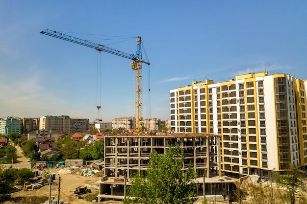 Appartement of kantoor hoog gebouw in aanbouw. werkende bouwers en torenkranen op heldere blauwe hemel.