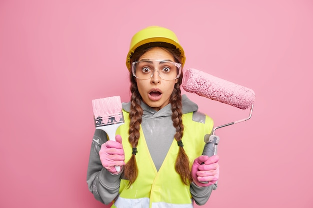 Appartement renovatie concept. geschokt drukke vrouwelijke onderhoudsmedewerker draagt een beschermende helmbril en uniform gebruikt bouwapparatuur voor de wederopbouw van het huis en reageert op iets verbluffends