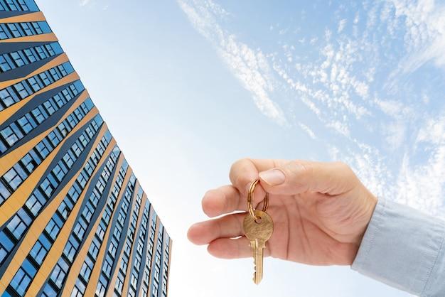 Appartement sleutel in de hand van een man. messing huisdeurslot sleutel. modern gebouw tegen de blauwe lucht. van onderaf bekijken.
