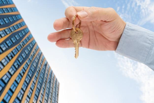 Appartementssleutel in de hand van een man. sleutel van het deurslot van messing. modern gebouw tegen de blauwe hemel. bekijk van onderen.