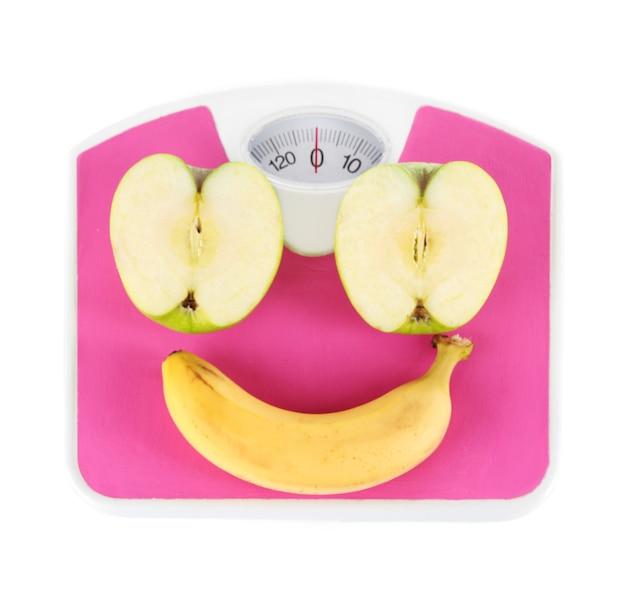 Appel en banaan op schalen op wit wordt geïsoleerd