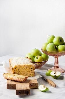 Appel- en kokosbroodcake en appels in een vaas op een tafel. ruimte kopiëren