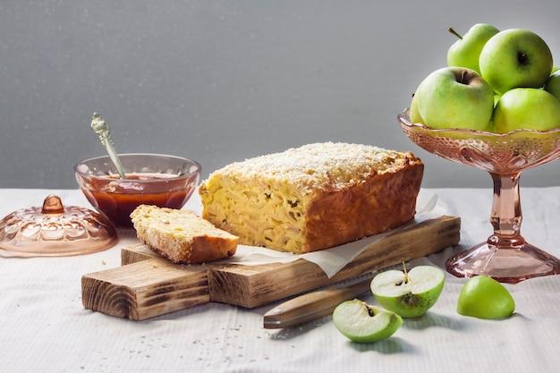 Appel- en kokosbroodcake en appels in een vaas op tafel