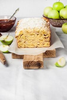 Appel- en kokosnootcake op houten snijplank en appels in een vaas. ruimte kopiëren