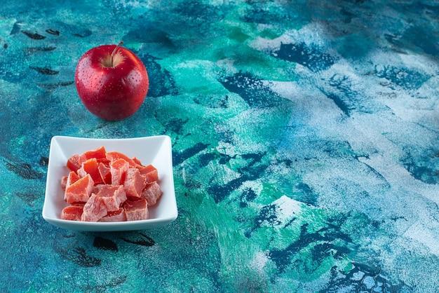 Appel en rode marmelade in een kom op blauw.