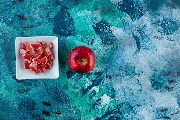 Appel en rode marmelade in een kom, op de blauwe tafel.