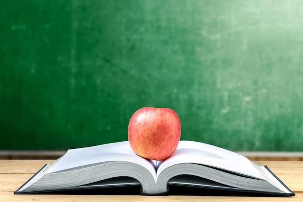 Appel in het midden van geopend boek op houten tafel met schoolbord