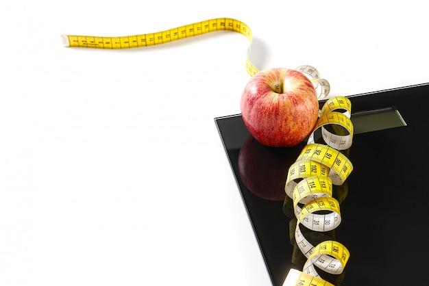 Appel liggend op de weegschaal terwijl de liniaal erop gebogen is.