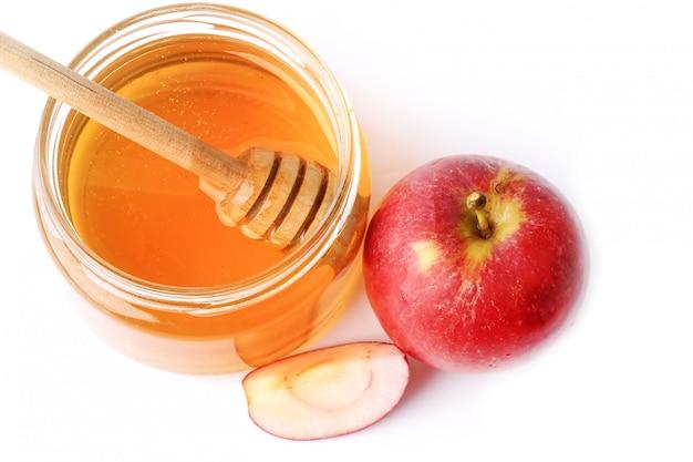 Appel met honing die op een witte achtergrond wordt geïsoleerd