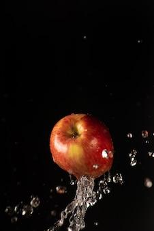 Appel met mooie scheut water met zwarte achtergrond en selectieve aandacht.