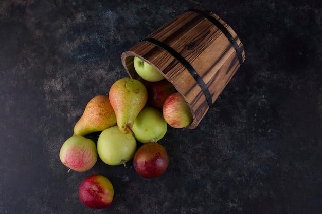 Appel, perzik en peren uit een houten emmer