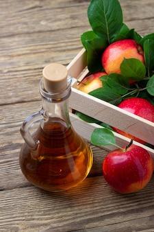 Appelazijn en verse rode appel op een houten achtergrond