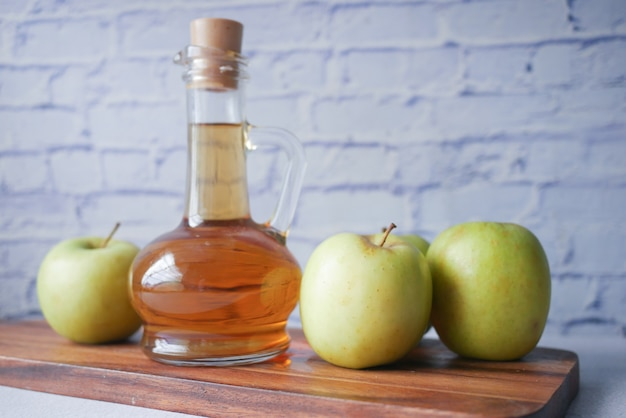 Appelazijn in glazen fles met verse groene appel op tafel