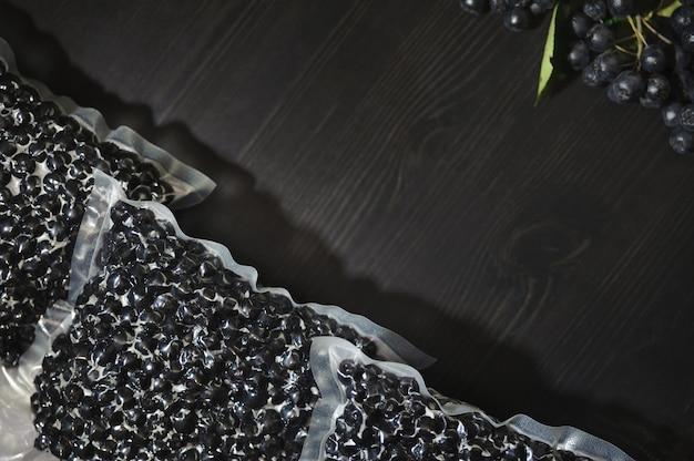 Appelbesbessen (aronia melanocarpa) zijn verpakt in vacuümzakken en zwarte bessen op een donkere tafel.