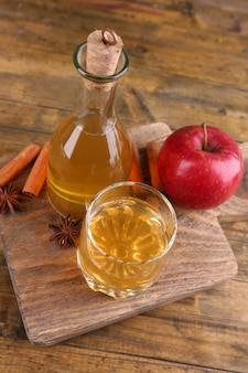 Appelcider in glazen fles met kaneelstokjes en verse appels op snijplank, op houten muur