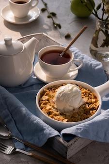 Appelcrumble met een bolletje vanille-ijs en thee op een houten dienblad. ontbijt concept.