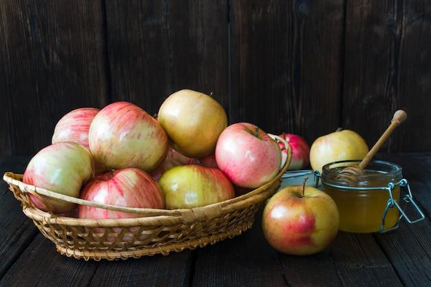Appelen in een mand en honing op een zwarte achtergrond