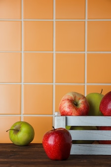 Appelen in een witte houten doos op een houten en oranje tegelachtergrond. zijaanzicht.