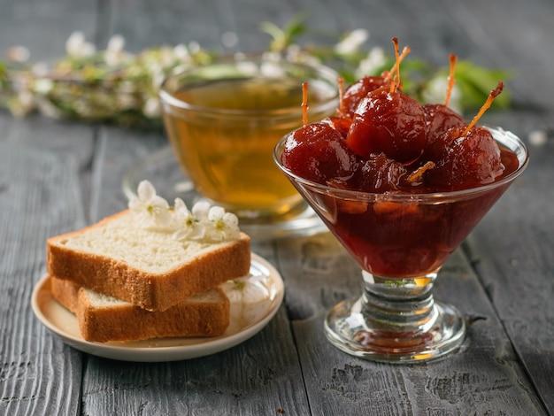 Appeljam, brood en thee op een zwarte houten tafel. zelfgemaakte zoetigheden volgens oude recepten.