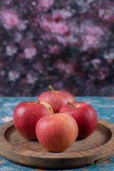 Appels beong geserveerd op ronde houten plaat.