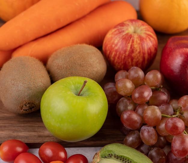 Appels, druiven, wortelen en sinaasappels bij elkaar op de grond.