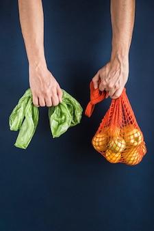 Appels en citroenen in een oranje koordzak in de hand van één man in een andere plastic zak