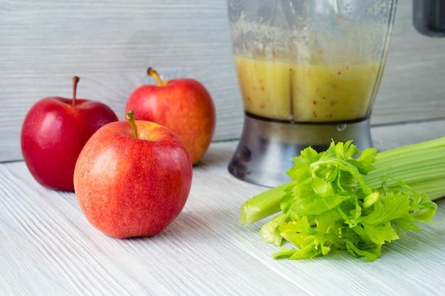 Appels en een bosje selderij en een keukenmachine met een smoothie op een witte tafel