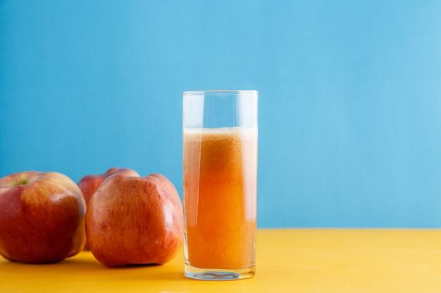 Appels en een glas natuurlijk appelsap op geelblauw