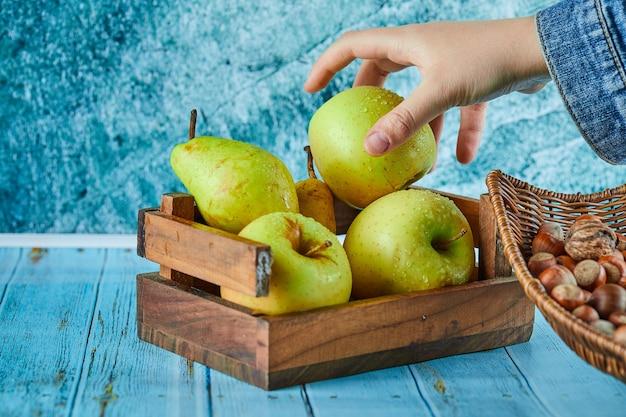 Appels en peer in houten mand en kom met hazelnoten op blauwe oppervlakte.