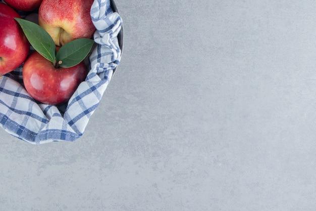 Appels gewikkeld in een handdoek op marmer.