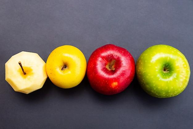 Appels groen geel rood en appel zonder schil op een zwarte muur