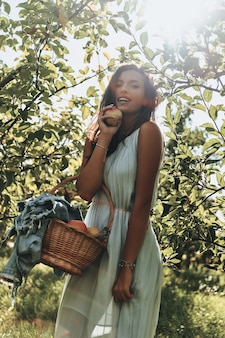 Appels houden dokters weg! aantrekkelijke jonge vrouw die een mand vol appels draagt en glimlacht terwijl ze in de tuin staat