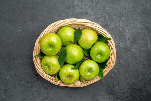 Appels in de mand de smakelijke appels met groene bladeren in de mand