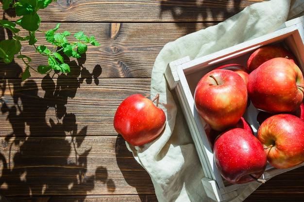 Appels in een doos in de buurt van planten