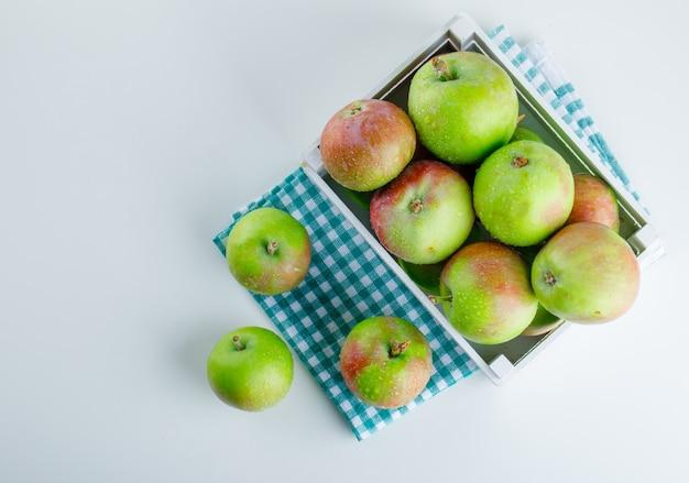 Appels in een houten kist op wit en picknickdoek.