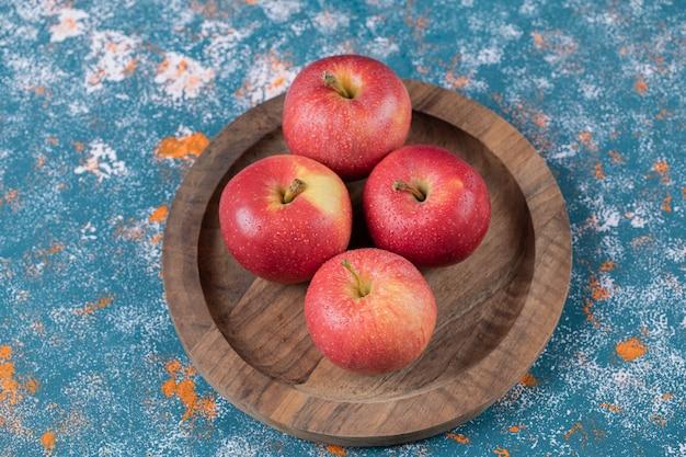 Appels in een houten plaat op een blauwe textuurtafel.