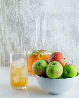 Appels in een kom met dranken zijaanzicht op wit en grungy