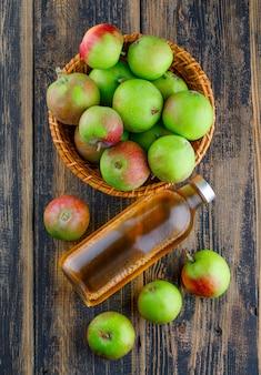 Appels in een mand met fles drank bovenaanzicht op een houten achtergrond