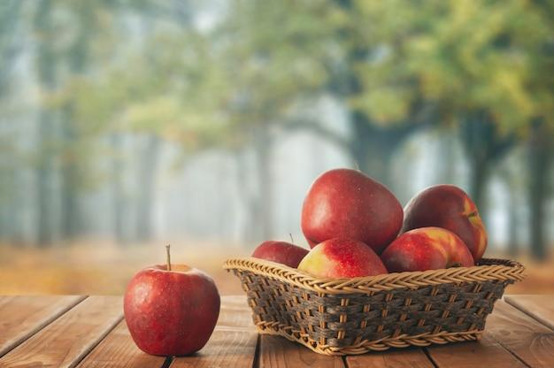 Appels in een mandje tegen met een herfsttuin
