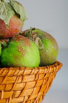 Appels in een rieten mand met bladerenclose-up op wit
