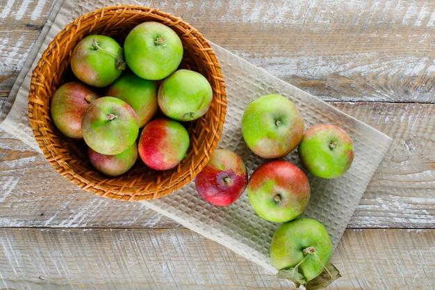 Appels in een rieten mand op houten en keukendoek.