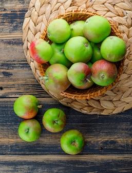 Appels in een rieten mand op houten en placematachtergrond. bovenaanzicht.