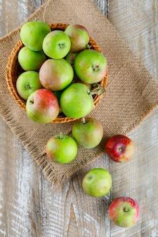 Appels in een rieten mand op houten en stuk zak. bovenaanzicht.