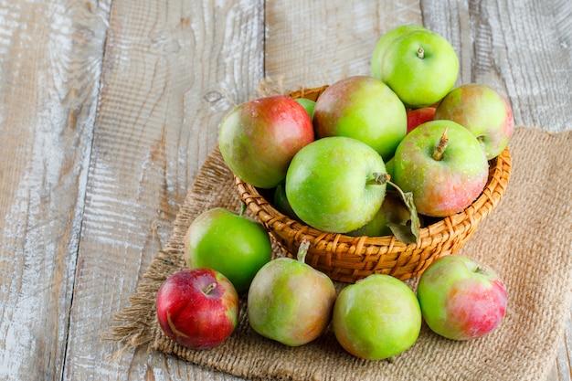 Appels in een rieten mand op houten en stuk zak. hoge kijkhoek.