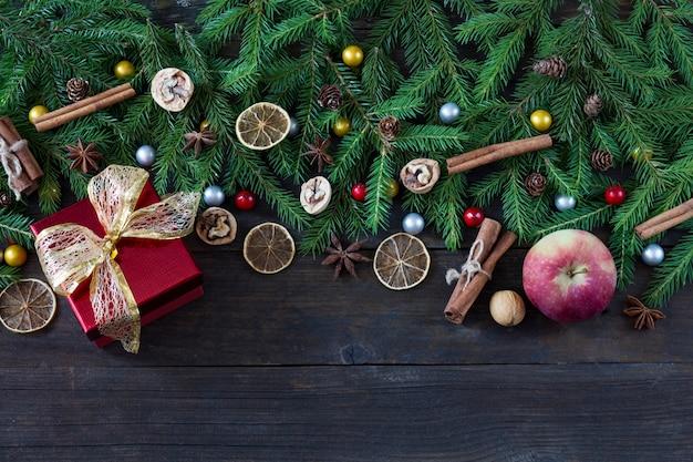 Appels, kaneel, schijfjes citroen, walnoten, kegels en een rode doos met een geschenk met een gouden strik