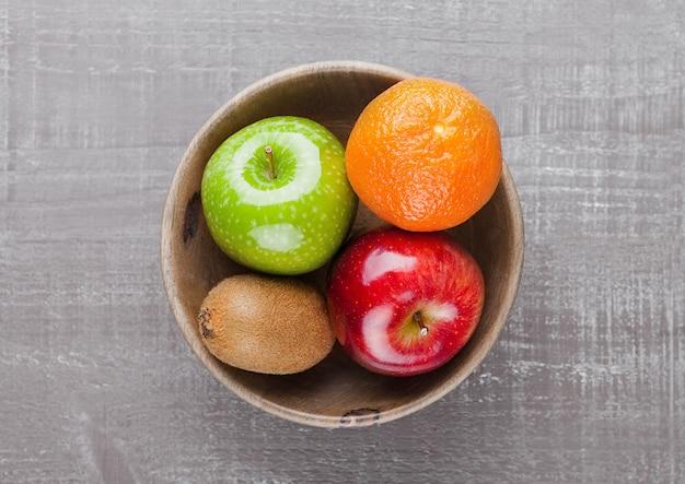 Appels met kiwi en sinaasappel in houten kom op tafel