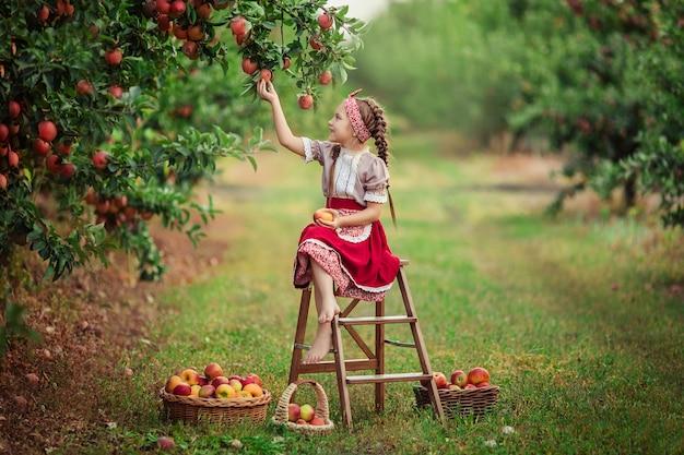 Appels oogsten op het platteland in de tuin. mooi meisje in vintage kleding een rode rok en een solokha zit in de buurt van rieten manden met appels