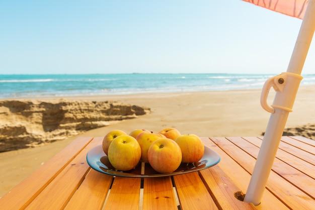 Appels op een bord op het strand