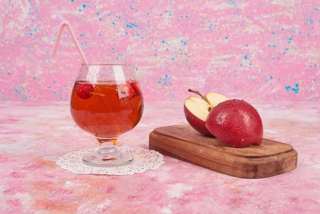 Appels op een houten bord met een glas sap rond.