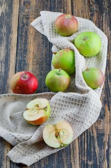 Appels op houten en keukenhanddoekachtergrond, hoge hoekmening.